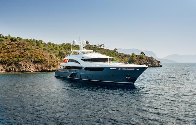Il grande yacht di lusso rimane nel mare intorno all'isola su uno sfondo di cielo