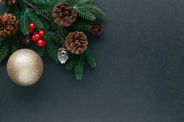 Il granito nero in bianco isolato decora con il pino e i coni, le sfere dell'agrifoglio e la sfera dorata di scintillio di lusso