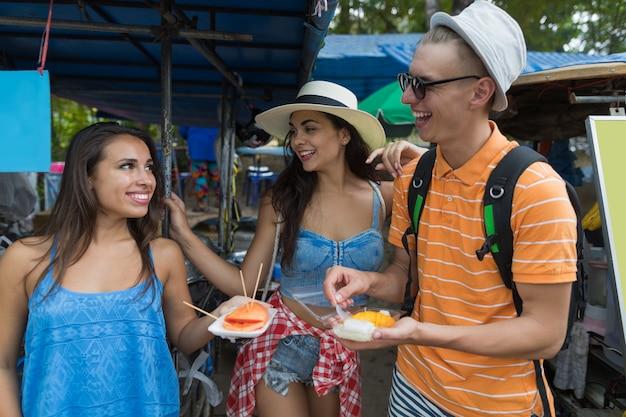 Il gruppo allegro di amici mangia la frutta fresca che esplora la città asiatica
