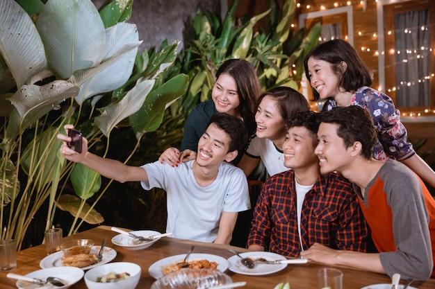 Il gruppo asiatico del migliore amico prende il selfie con lo smartphone mentre ha festa in giardino