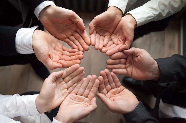 Il gruppo di affari si unisce le mani in palme del cerchio su, concetto della crescita