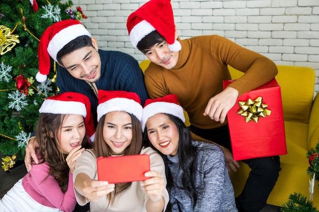 Il gruppo di amici asiatici che prendono insieme il selfie con l'amico dallo smartphone a casa durante la festa di notte di natale o il nuovo anno celebra il partito. felice inverno natale e felice anno nuovo concetto di partito