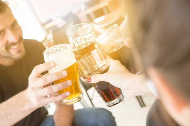 Il gruppo di amici che godono della sera beve in barra