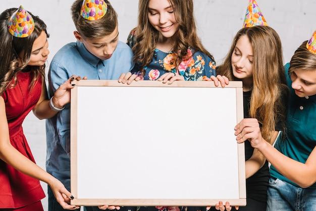 Il gruppo di amici che portano il cappello del partito che esamina la struttura in bianco bianca tiene da loro