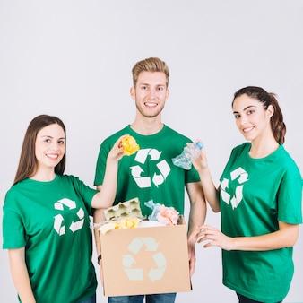 Il gruppo di amici felici che tengono la scatola di cartone con ricicla gli oggetti