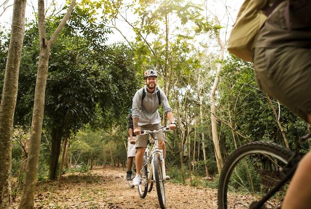 Il gruppo di amici guida insieme la mountain bike nella foresta