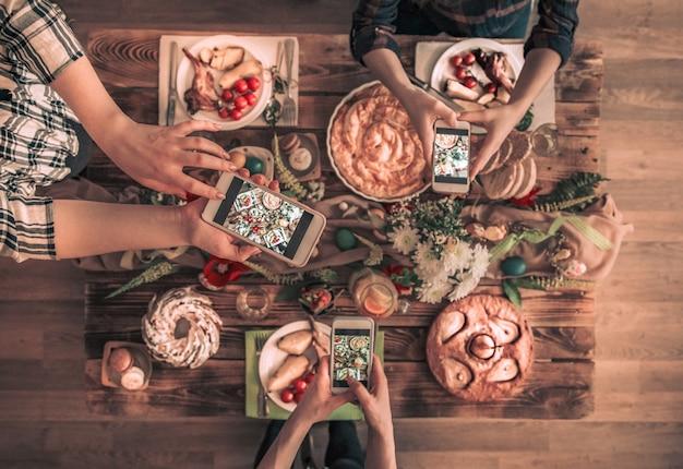 Il gruppo di amici scatta una foto con il cellulare prima di pranzare. vista dall'alto.