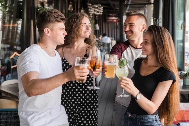 Il gruppo di amici sorridenti che tengono le bevande dell'alcool ha messo produrre il pane tostato
