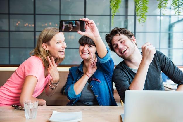 Il gruppo di amici sta prendendo insieme la foto del selfie
