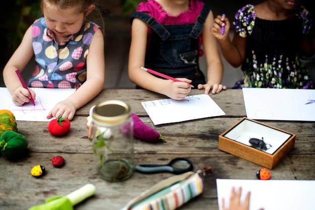 Il gruppo di asilo scherza gli amici che disegnano l'arte di immaginazione sulla carta