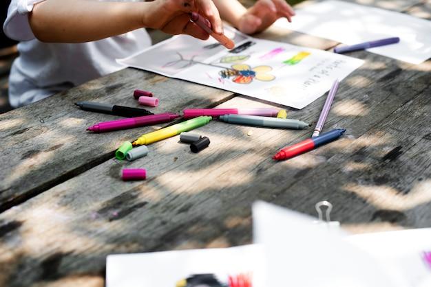Il gruppo di asilo scherza gli amici che disegnano la classe di arte all'aperto