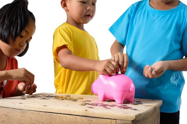 Il gruppo di bambini asiatici sta aiutando a mettere le monete nel porcellino salvadanaio isolato su fondo bianco