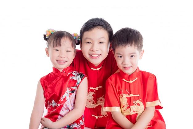 Il gruppo di bambini che indossano il costume tradizionale cinese sorride sopra fondo bianco