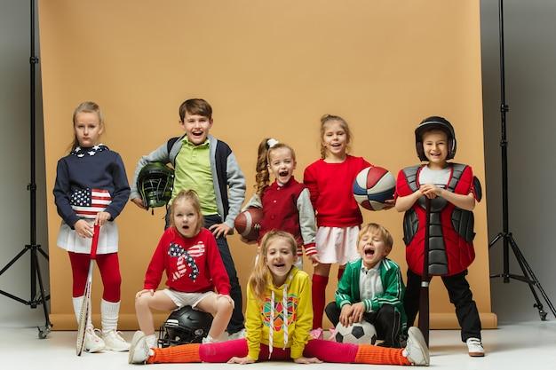 Il gruppo di bambini felici mostra sport diversi.