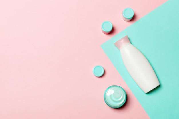 Il gruppo di bottiglia di plastica del bodycare composizione piana in disposizione con i prodotti cosmetici sullo spazio vuoto del fondo rosa e blu per voi progetta. set di contenitori cosmetici bianchi, vista dall'alto con spazio di copia