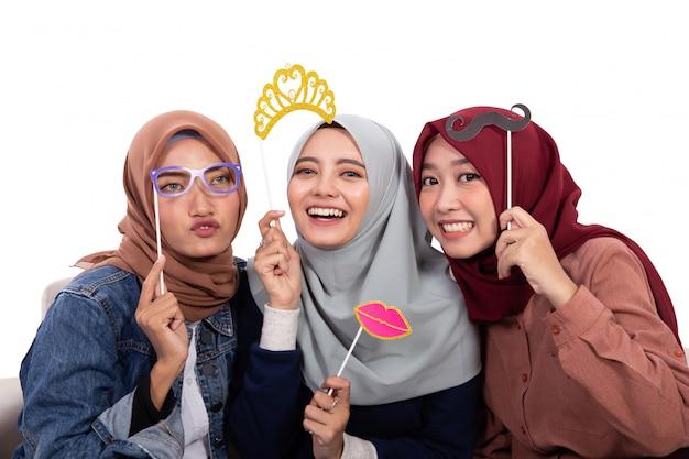 Il gruppo di donna velata che tiene la maschera e il sorriso esaminano la macchina fotografica