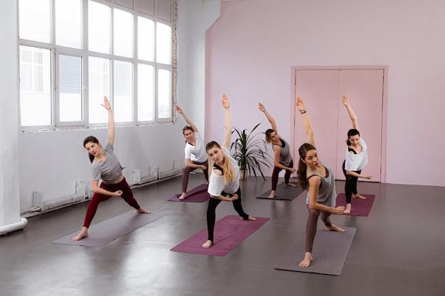 Il gruppo di donne che fanno i pilates si esercita in palestra