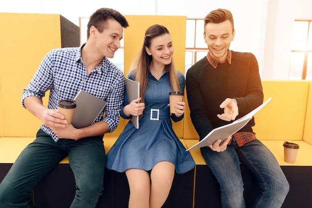 Il gruppo di gente creativa sta discutendo con la tazza di caffè.