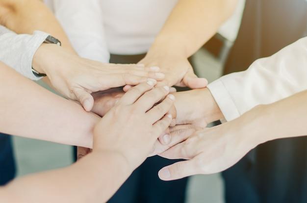 Il gruppo di gente di affari che mette insieme le loro mani di squadra unisce le mani