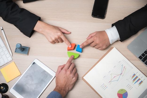 Il gruppo di gente di affari che monta il puzzle e rappresenta il supporto del gruppo e aiuta il concetto