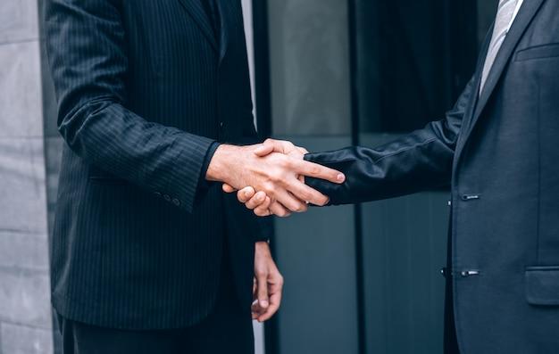 Il gruppo di gente di affari che stringe le mani con l'associazione mentre sta con i colleghi dopo finisce una negoziazione di riunione, concetto di lavoro di squadra