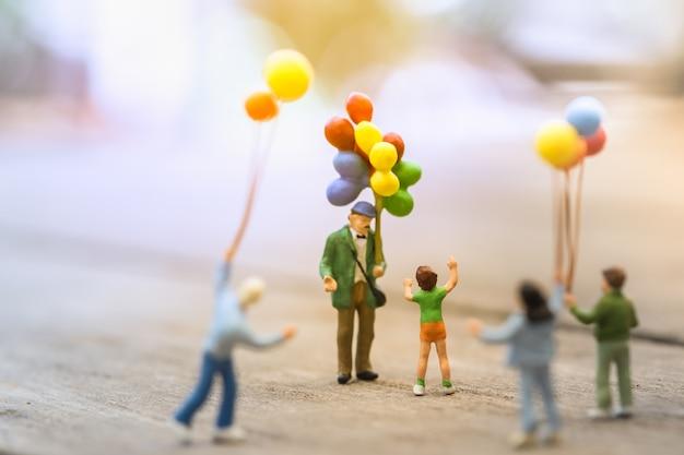 Il gruppo di gente miniatura della miniatura dei bambini sta stando e camminando intorno ad un venditore del pallone dell'uomo