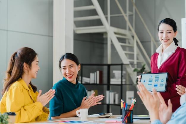 Il gruppo di giovani creativi asiatici in abbigliamento casual intelligente che discute di affari festeggia dando cinque dopo aver affrontato la sensazione di essere felici e aver firmato un contratto o un accordo in ufficio. concetto di lavoro di squadra del collega.