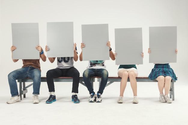 Il gruppo di giovani si siede la tenuta, fucilazione in bianco dello studio del bordo del segno
