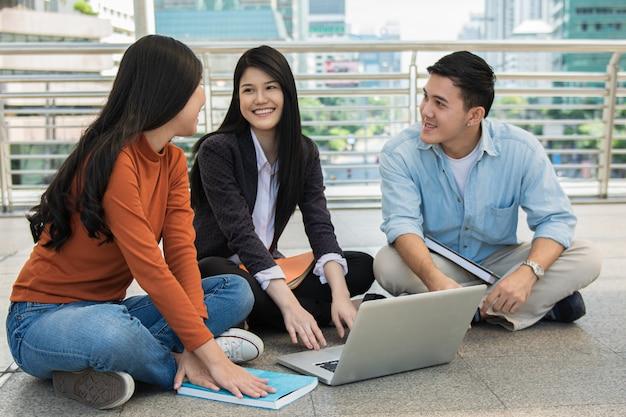 Il gruppo di giovani studenti studia e legge insieme nel corridoio dell'università durante la pausa con libri e computer portatile