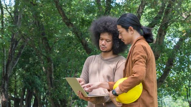 Il gruppo di ingegneria asiatica dell'appaltatore dell'uomo presenta il progetto con il computer portatile in giardino verde.