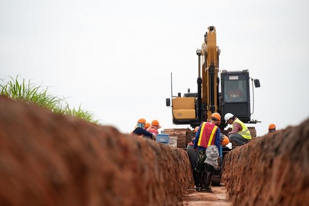 Il gruppo di lavoratore e l'ingegnere di costruzione indossano il drenaggio dell'acqua di scavo dell'uniforme di sicurezza