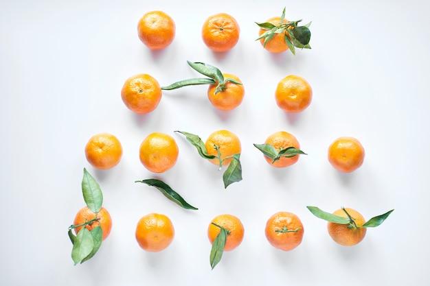 Il gruppo di mandarini freschi arancio con le foglie verdi si trova su una superficie bianca