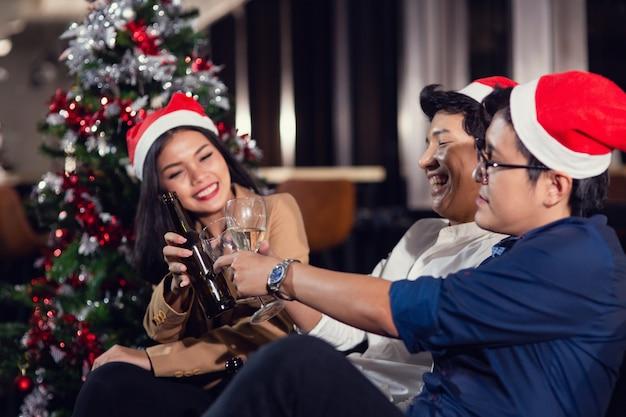 Il gruppo di multi generazione che beve champagne e l'alcool che porta il cappello di santa gode della festa di natale