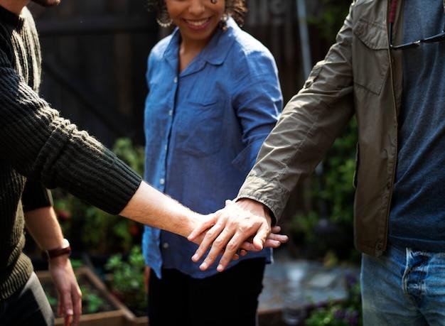Il gruppo di persone che le mani degli agricoltori impilano insieme il supporto