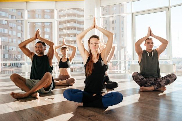 Il gruppo di persone che si siedono nel loto posa allo studio di yoga
