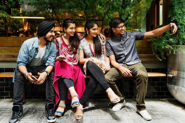 Il gruppo di persone indiane sta prendendo selfie insieme