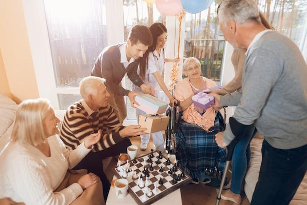 Il gruppo di persone si congratula con una donna per il suo compleanno.