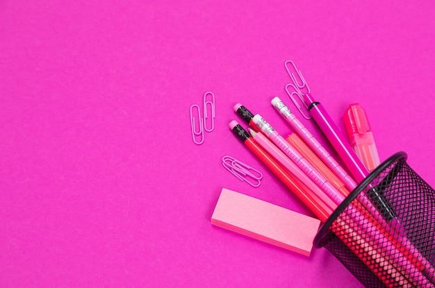 Il gruppo di prodotti di cancelleria di colore rosa è rovesciato dalla scatola della matita sul flatlay di superficie rosa isolato