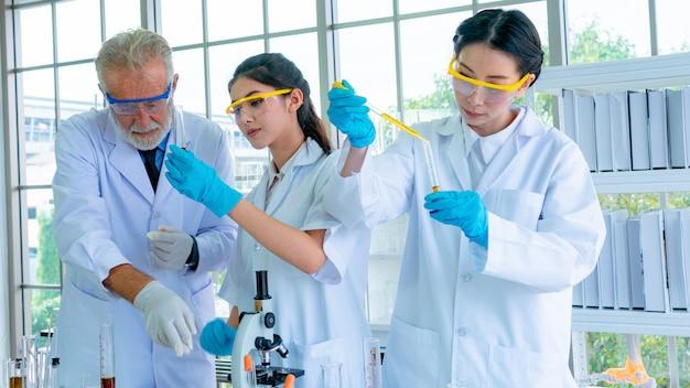 Il gruppo di professore ricercatore scienziato con abito bianco prepara il liquido chimico di prova
