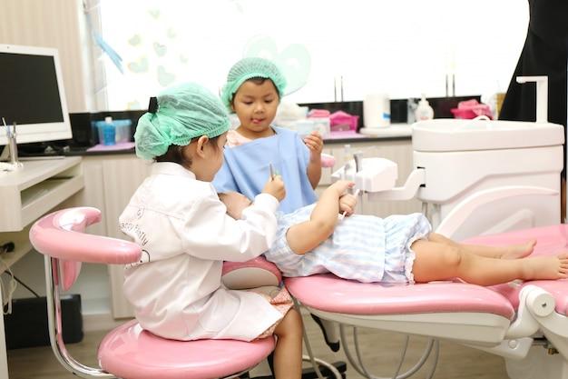 Il gruppo di ragazze asiatiche usa l'attrezzatura del dentista per pulire i denti per prevenire il mal di denti e il benessere