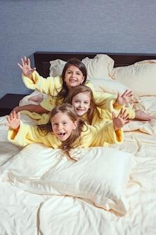 Il gruppo di ragazze che si divertono sul letto
