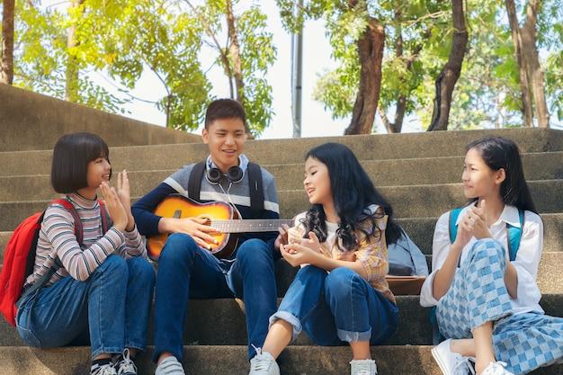 Il gruppo di studente del bambino che gioca la chitarra e che canta le canzoni insieme nel parco dell'estate