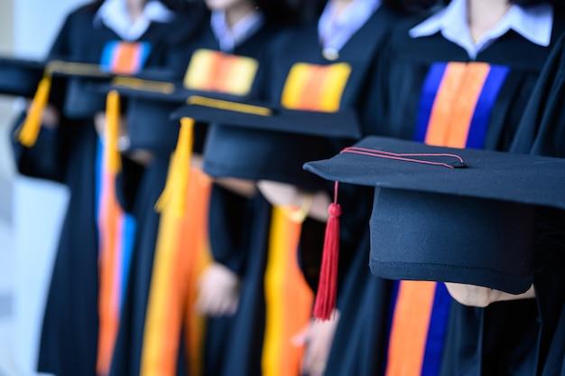 Il gruppo di studenti laureati portava un cappello nero, cappello nero, alla cerimonia di laurea all'università.
