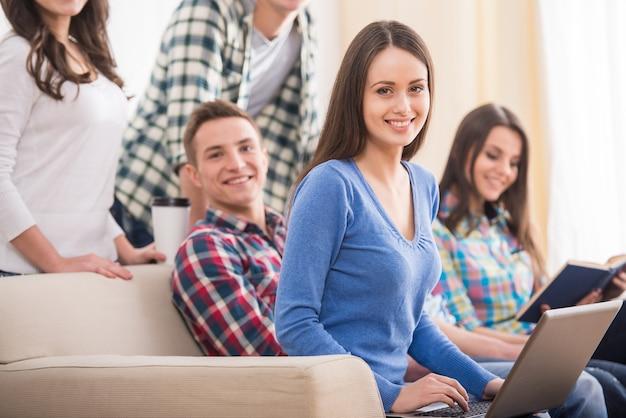 Il gruppo di studenti sta sedendosi sul sofà con il computer portatile e il libro.