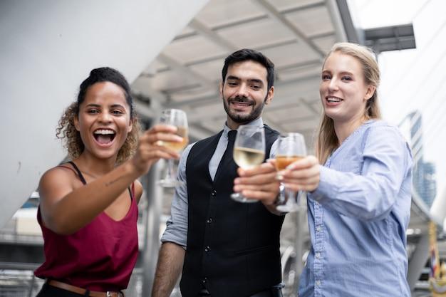 Il gruppo di uomini d'affari celebra bevendo vino.