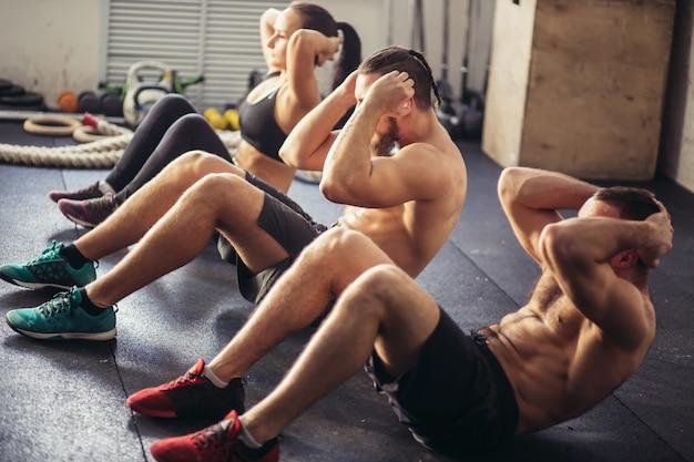 Il gruppo di uomini e donne adulti atletici che eseguono si siedono sugli esercizi