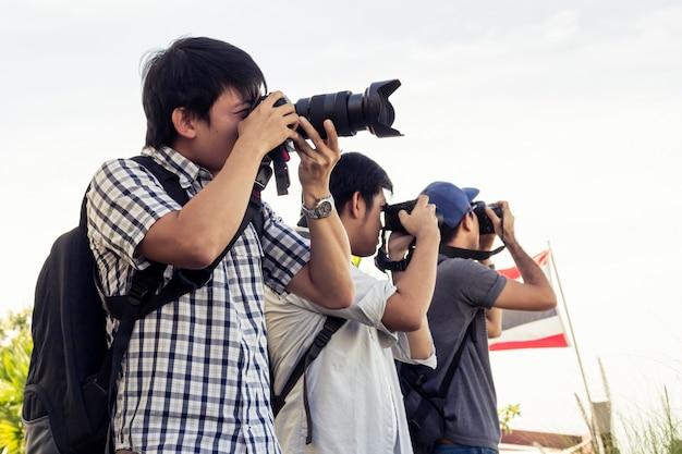 Il gruppo di uomini sta stando la fotografia sulla riva del fiume in tailandia.