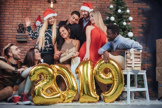 Il gruppo di vecchi amici allegri comunica l'un l'altro. il nuovo anno 2019 sta arrivando. festeggia il nuovo anno in un'atmosfera accogliente