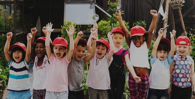 Il gruppo di viaggi della scuola dei bambini che imparano il divertimento sorridente attivo all'aperto
