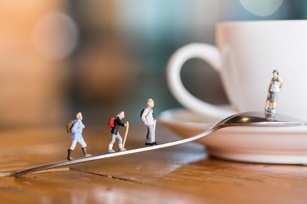 Il gruppo di viaggiatore sta e camminando sul cucchiaio al piatto della tazza di caffè caldo in caffetteria